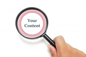 "A hand holding a magnifying glass over the words ""your content"" symbolizing a legal content audit"