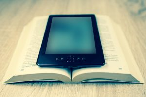 Ebook on top of open book on a wooden desktop symbolizing a content author delivering advanced writing in a traditional and modern formats