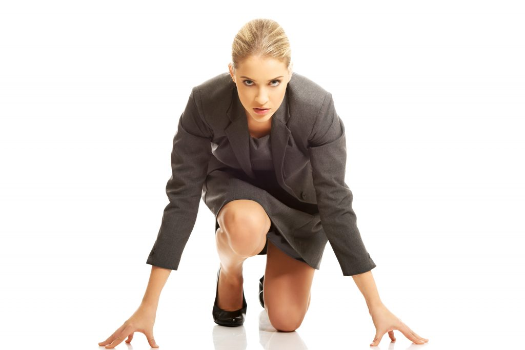 A female lawyer in professional attire crouched as in a starting position on a white background to signify the need to start attorney advertising to have a successful law practice