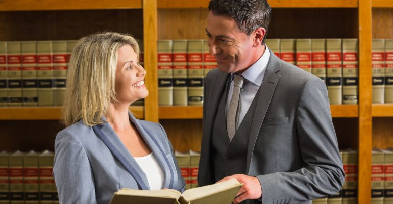 Succesful Law Practice Counselors smiling and talking to each other holding an open ethics book discussing attorney advertising with a bookshelf and law books in the background