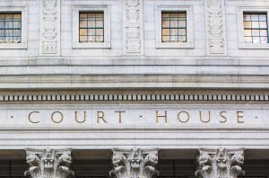 Court House from the front with the words court house visible etched in stone overlooking columns as the entrance to an actual court house