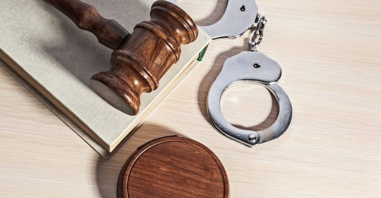 Arrested for a felony blog writing sample image showing judges gavel on top of a book with handcuffs