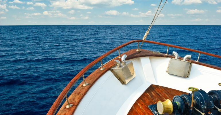 Blog Images for REgister your Vessel Blog Writing Sample depicting the bow of a yacht on the ocean with the sky in the horizon