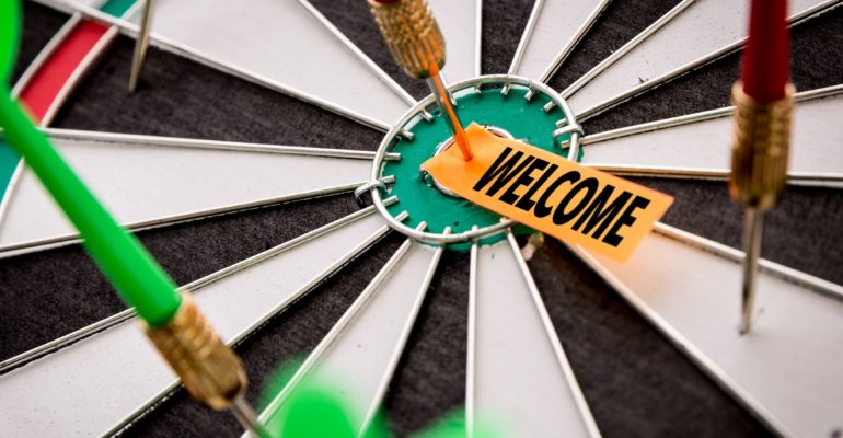 Dart board signifying strategy with one dart embedded in the bulls eye circle with a welcome tag pinned to the bulls eye.
